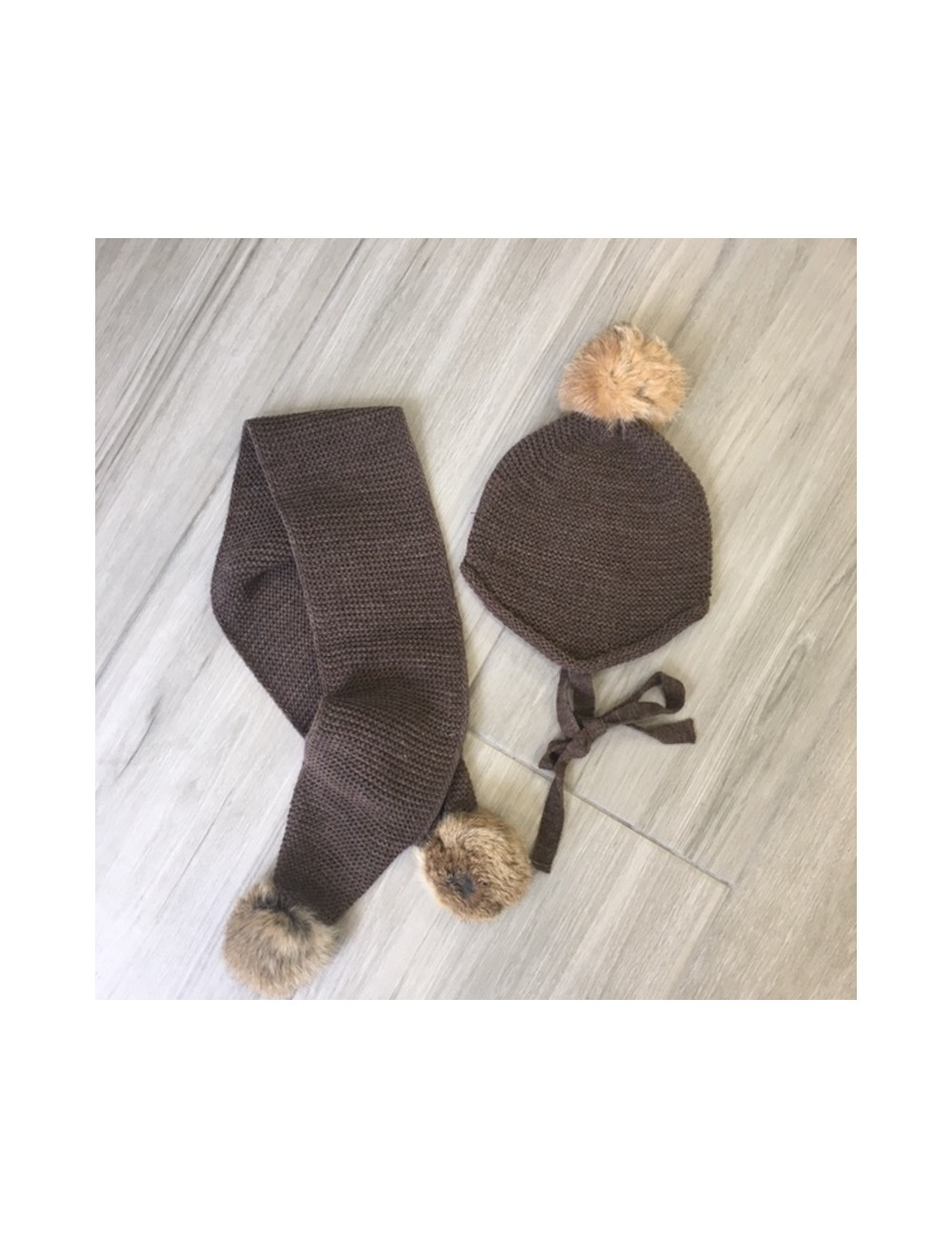 Conjunto formado por gorro y bufanda color marron chocolate con borlas en color natural de Paloma de la O