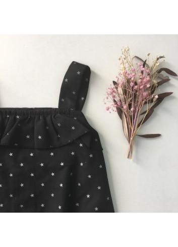 Pelele negro con estrellas plateadas y detalle de volante en la parte superior, de la marca Mia y Lia.