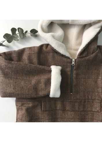 Cazadora tipo canguro  de cuadros marrón con una sutil raya azul, con capucha y forro de borreguito de la marca Mia y Lia.