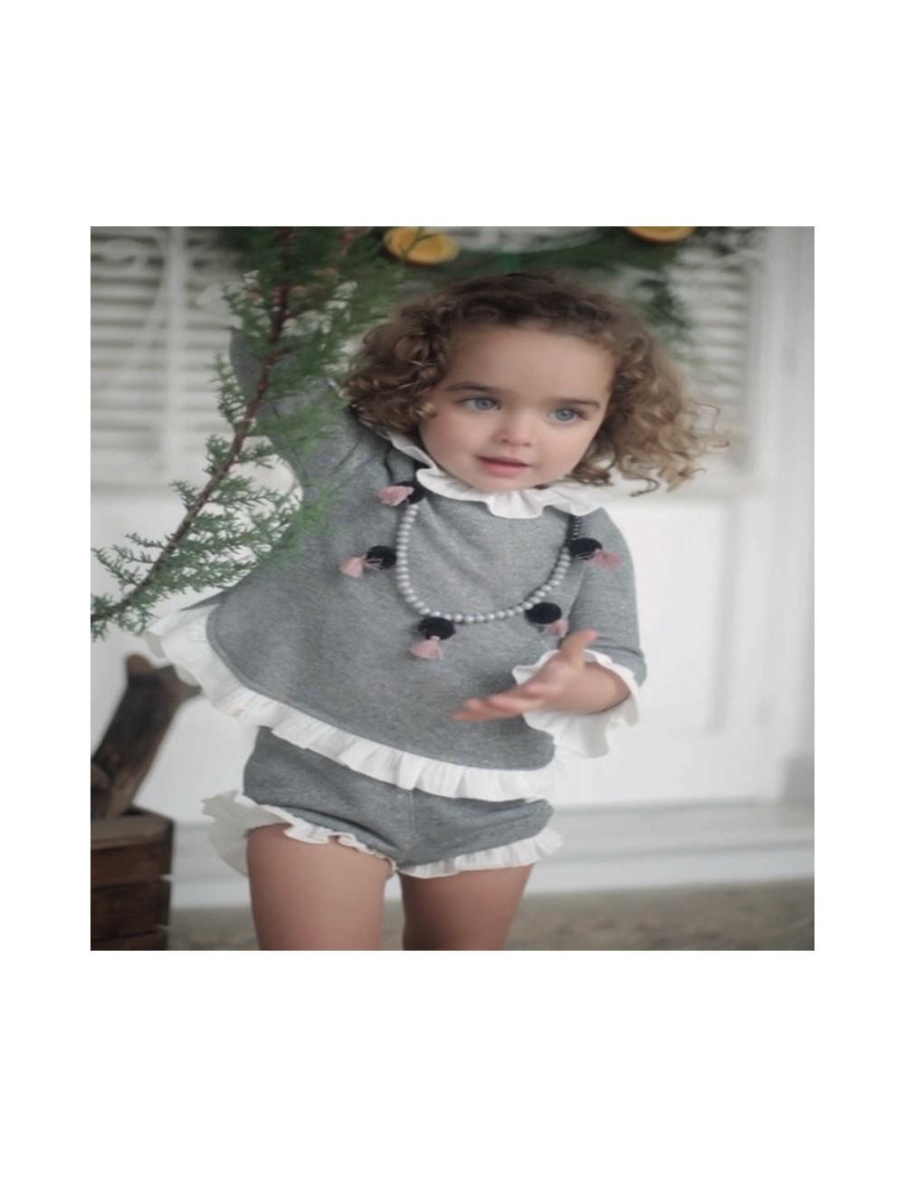 Conjunto de punto formado por pololo y jersey gris con lurex, con detalles de volantitos blancos de la marca Pilar Batanero
