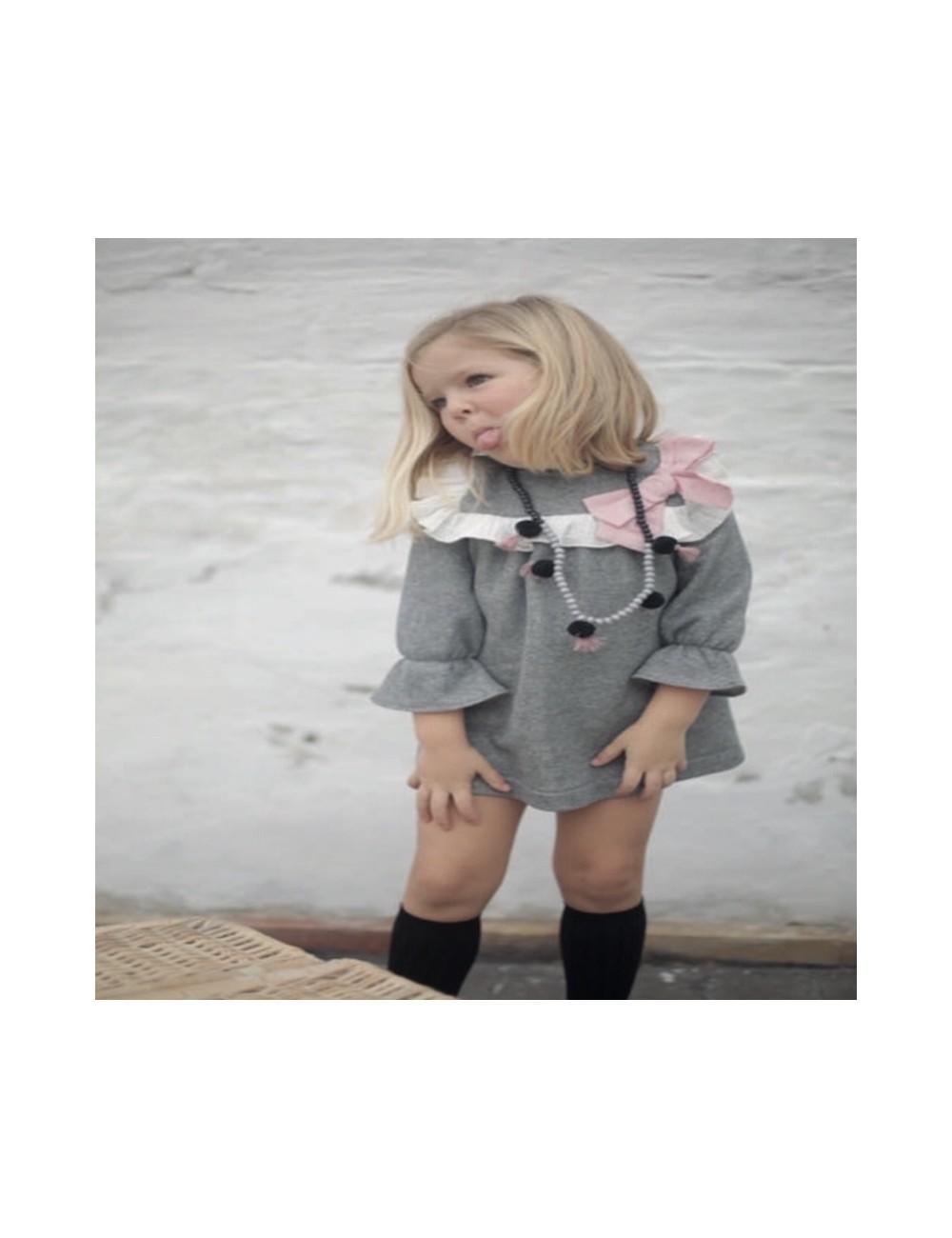 Vestido gris lurex con detalle de volante en el canesu y lazo de plumetti rosa de la marca Pilar Batanero