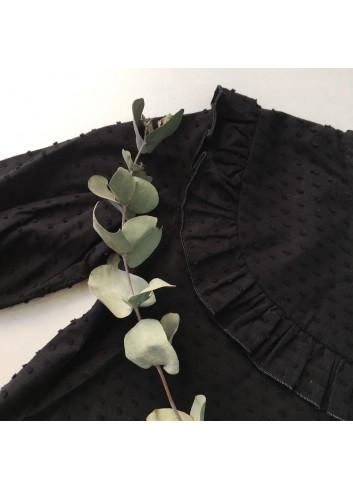 Blusa básica negra de plumeti de niña con detalle de volante en el canesú del a marca Mia y Lia. Disponible también en blanco.